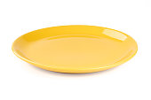 Pastel yellow colored plate isolated on white background, front view, clipping path, without the cast shadow, included.