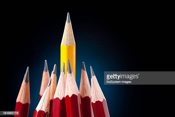 A yellow pencil surrounded by red pencils for leadership