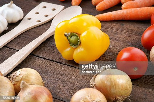 Yellow pepper with vegetables and cooking spoons : Stock Photo