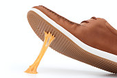 Chewing gum stuck on a brown shoe against white background
