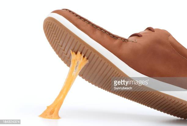 Yellow piece of gum stuck on bottom of brown shoe