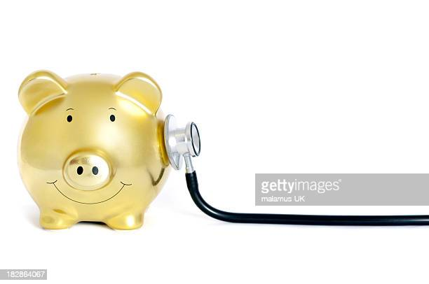 Yellow piggy bank with stethoscope on his side