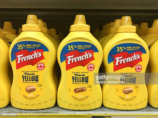 Yellow plastic squeeze bottles of French's mustard sauce displayed in neat rows on a store shelf