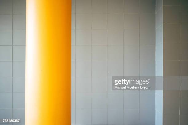Yellow Pole Against Tiled Wall