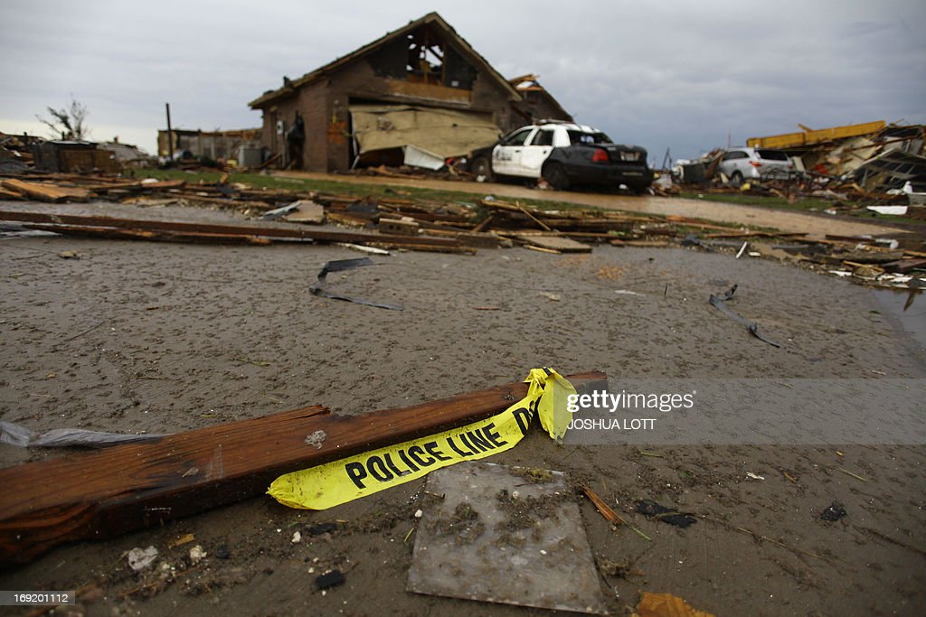 Yellow police tape sits near a damaged Oklahoma Police car outside of a destroyed home on May 21, 2013 in Moore, Oklahoma. Families returned to a blasted moonscape that had been an American suburb Tuesday after a monstrous tornado tore through the outskirts of Oklahoma City, killing at least 24 people. Nine children were among the dead and entire neighborhoods vanished, with often the foundations being the only thing left of what used to be houses and cars tossed like toys and heaped in big piles. AFP PHOTO/Joshua LOTT