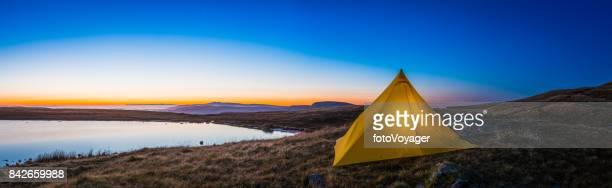 Yellow pyramid tent illuminated sunrise in idyllic mountain wilderness panorama