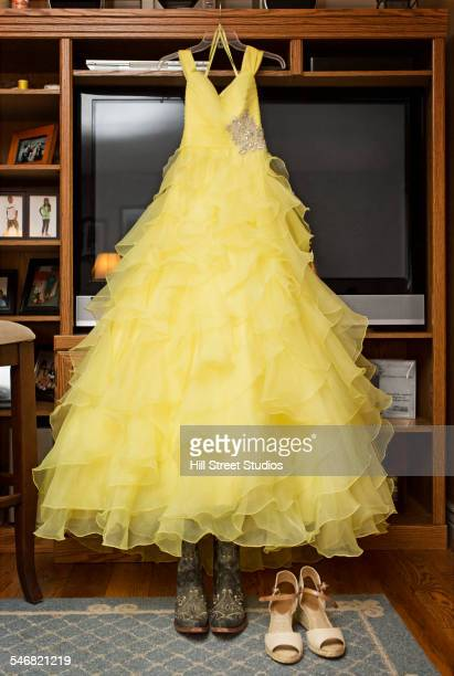 Yellow quinceanera dress hanging in living room