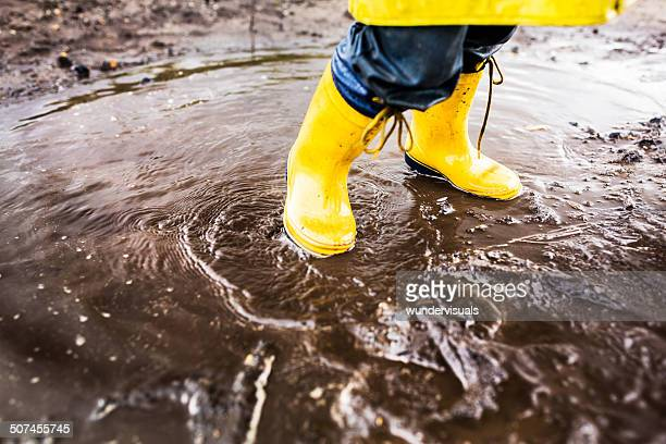 Yellow Rainboots In Puddle