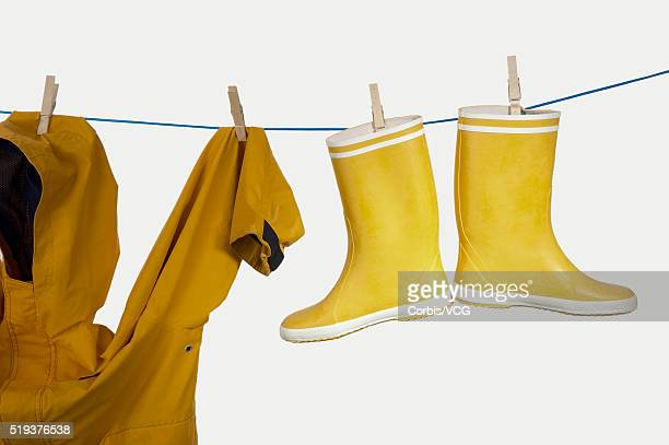 Yellow Raincoat and Galoshes Hanging on Clothesline