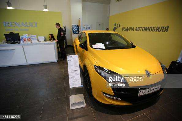 A yellow Renault Megane RS vehicle stands on display inside a Renault SA automobile dealership in Moscow Russia on Friday March 28 2014 Foreign...