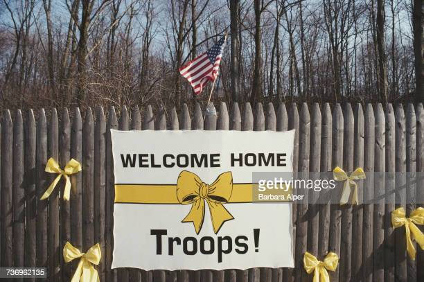 Yellow ribbons tied to a fence a US flag and a banner with a yellow ribbon image and the words 'Welcome Home Troops' after the First Gulf War USA...