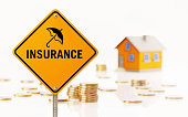 Yellow road sign in front of a yellow toy house on white background. Coins are scattered on white ground. Insurance text writes on yellow road sign with an umbrella icon representing insurance concept