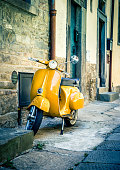 Yellow scooter in antique tuscan Cortona town