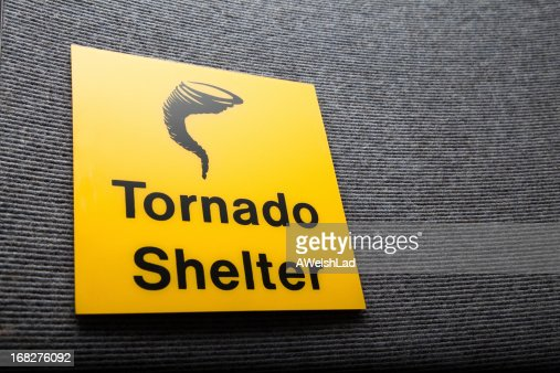 Yellow sign got a tornado shelter on a wall