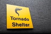 Yellow sign got a tornado shelter on a wall