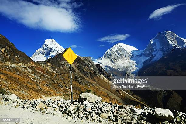 Yellow Sign Post By Stones With Mountain Peak In Background