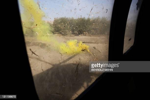 Yellow smoke marks the landing zone as a UH-60 Black Hawk