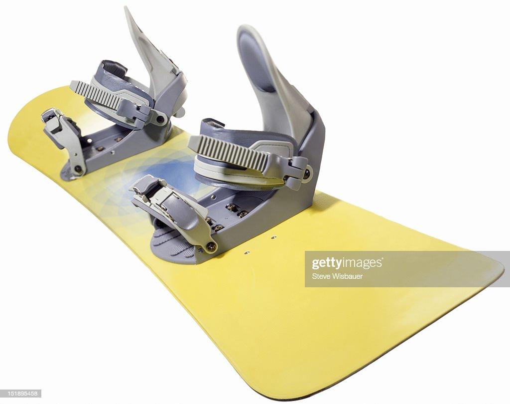 A yellow snowboard with grey bindings