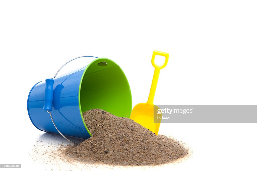 Yellow spade, and blue bucket with sand spilling out