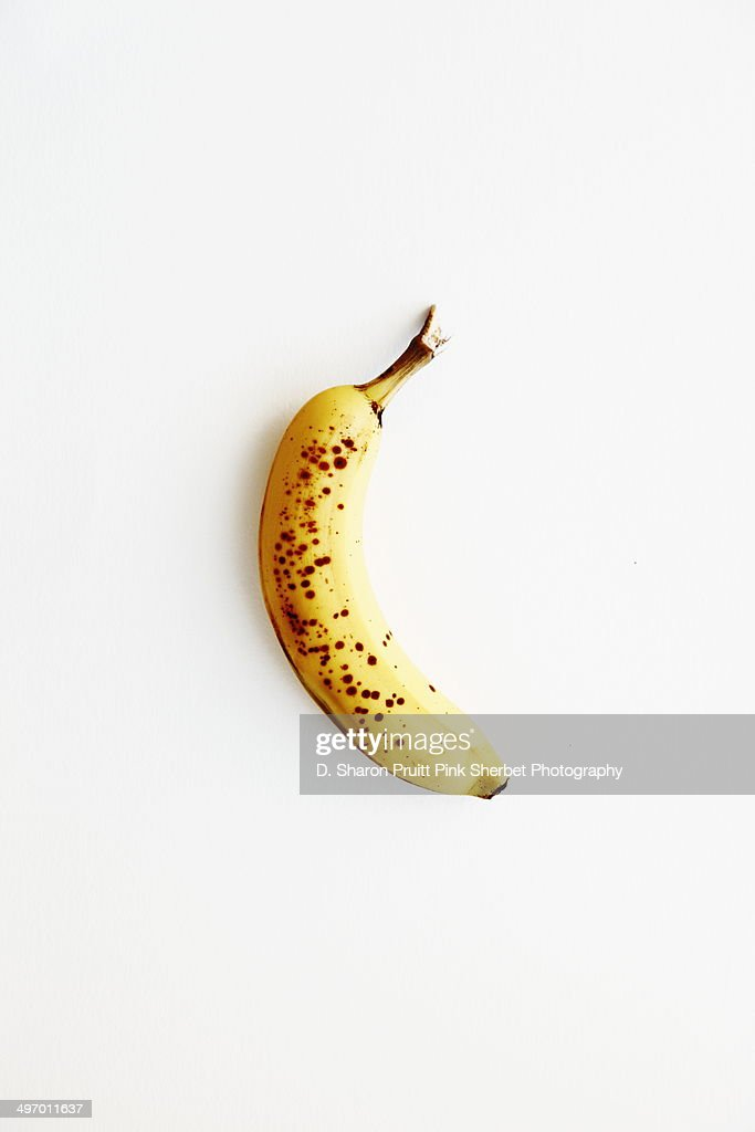 Yellow speckled banana on white
