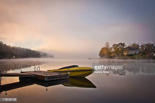 Yellow speedboat reflection at lake