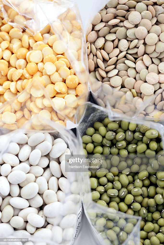 Yellow split peas, green lentils, haricot beans, mung beans in bags, overhead view