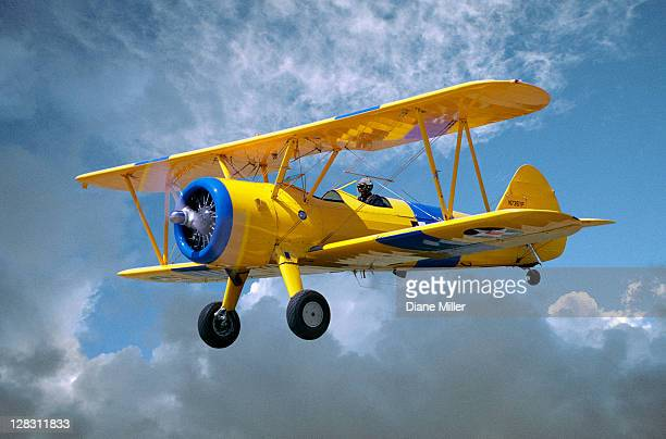Yellow Stearman 5YP bi-plane flying in cloudy sky