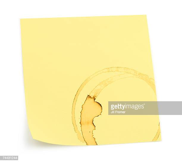 A yellow sticky note with a coffee stain