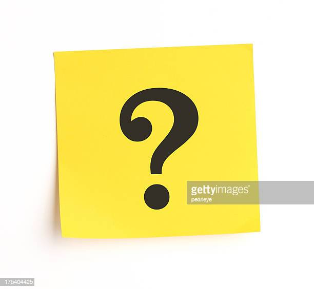Yellow sticky note with question mark stuck on white wall