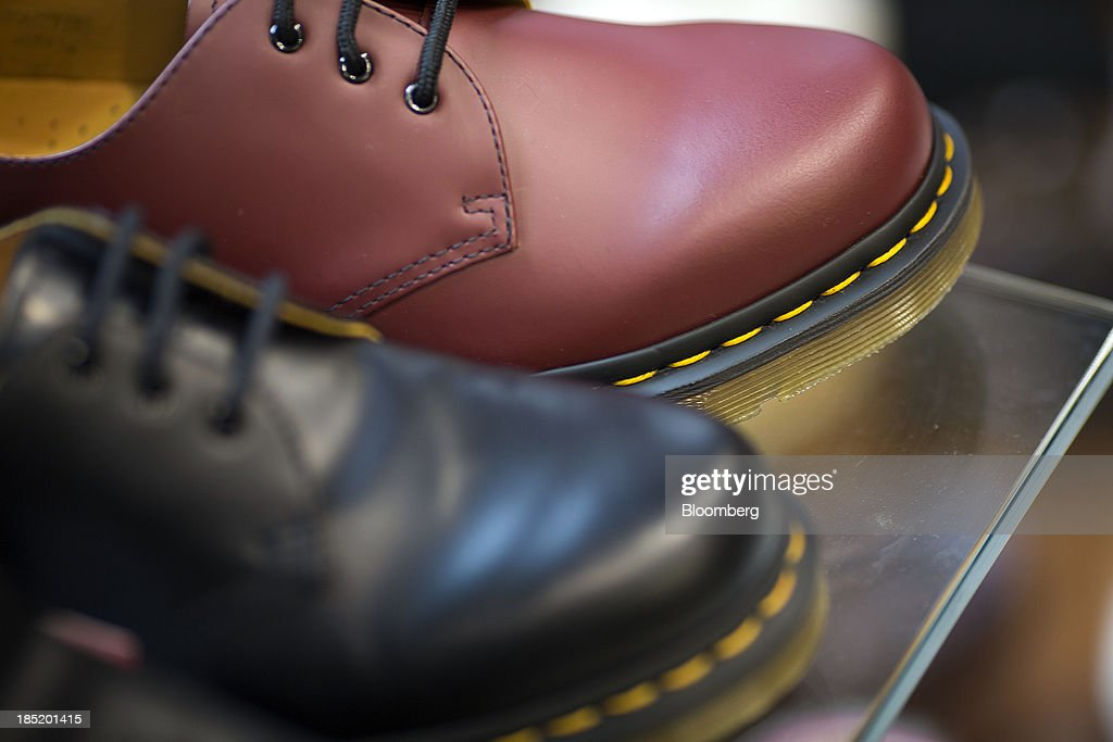 Yellow stitching is seen around the soles of Dr. Martens shoes inside a footwear store in London, U.K., on Friday, Oct. 18, 2013. Permira Advisers LLP, the London-based private-equity firm that owns clothing brand Hugo Boss, is in advanced talks to buy iconic British punk-boot maker Dr. Martens, said a person with knowledge of the negotiations. Photographer: Simon Dawson/Bloomberg via Getty Images