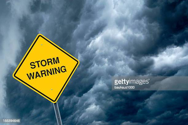 A yellow storm warning sign with storm clouds behind