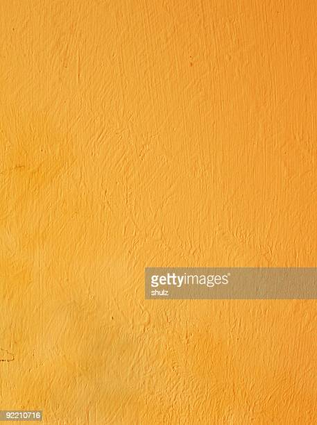 Yellow stucco wall in textured form