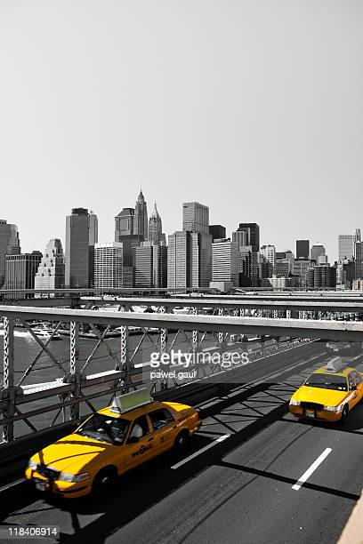 Yellow taxi cabs on Brooklyn bridge by day
