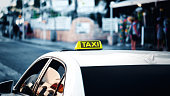 Yellow taxi sign. Taxi car on the street in city. Blue cold toning bokeh background. Banner size.