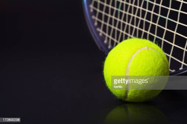 Yellow tennis ball and racket against black background