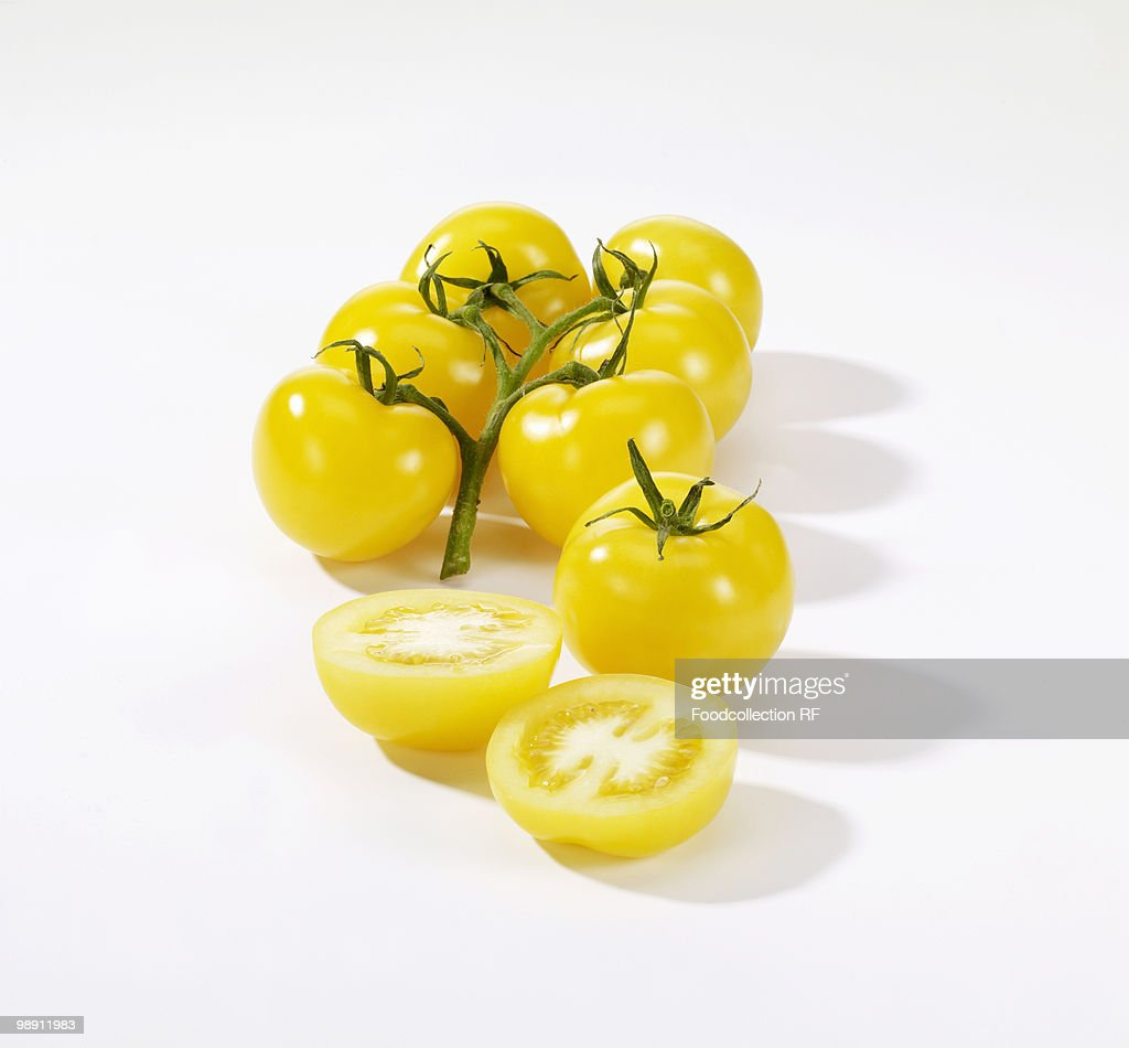 Yellow tomatoes on white background, close-up
