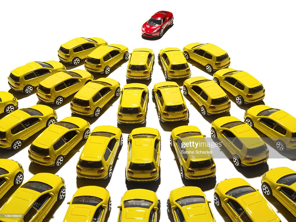 yellow toy cars grouped around red one