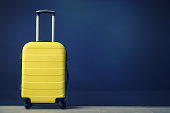 Travel bag against the wall. Yellow suitcase.