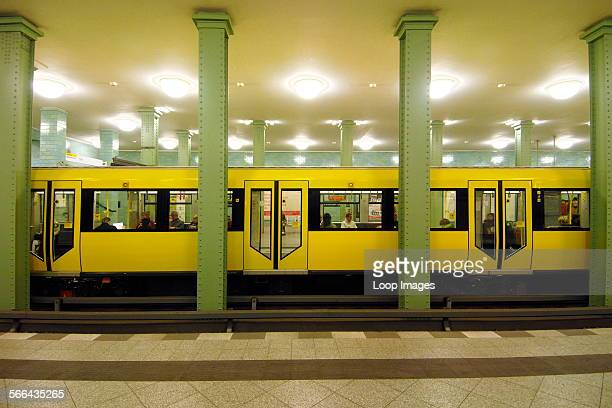 A yellow U Bahn train pulls up at the Alexanderplatz station in East Berlin