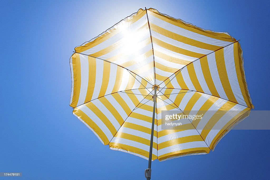Yellow umbrella against the sun and blue sky