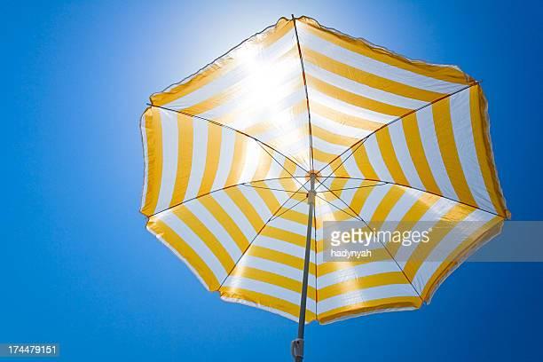Gelben Regenschirm gegen die Sonne und blauem Himmel