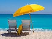 """""""Yellow Beach umbrella and deck chairs on the beach on a clear day on South beach, Miami"""""""