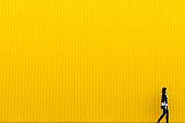 Girl walks near yellow wall