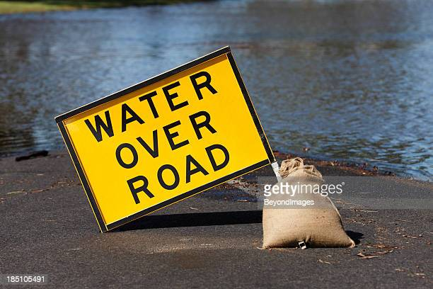 "Yellow ""Water Over Road"" hazard sign and flooded street"