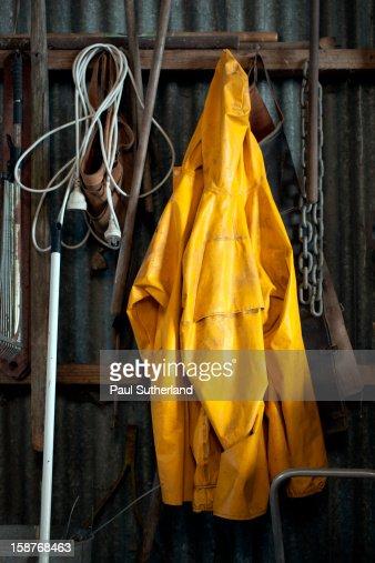 Yellow waterproof coat hanging in barn. : Stock Photo