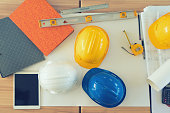 Yellow, white and blue helmet on table with tablet, grey folder,measuring tools and architectural project.
