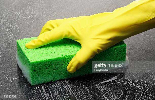 Yellow-gloved Hand Cleaning a Black Surface with a Sponge