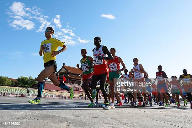 Yemane Tsegay of Ethiopia and Aadam Khamis of Bahrain lead the pack pass Tiananmen Gate during the Men's Marathon on day one of the 15th IAAF World...