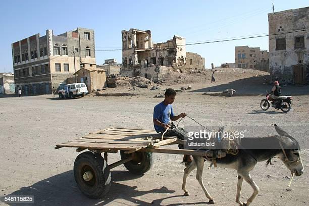 Yemen AlMukha Mocha Mokka Mokha boy on a donkeycart in front of ruins of houses