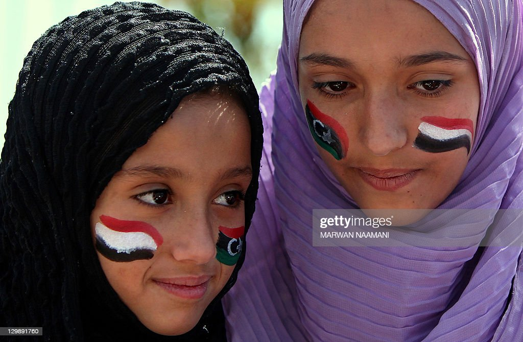 Yemeni anti-government protesters with their faces painted in the colours of the Libyan and the Yemeni flags attend the Friday noon prayer in Sanaa on October 21, 2011. Tens of thousands of demonstrators took to the streets of the Yemeni capital to demand the resignation of veteran President Ali Abdullah Saleh, galvanised by the death of Libya's Moamer Kadhafi. AFP PHOTO/MARWAN NAAMANI